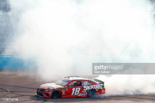 Kyle Busch, driver of the Skittles Toyota, celebrates with a burnout after winning the Monster Energy NASCAR Cup Series TicketGuardian 500 at ISM...