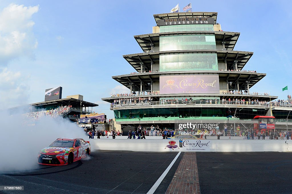 Kyle Busch, driver of the #18 Skittles Toyota, celebrates with a burnout after winning the NASCAR Sprint Cup Series Crown Royal Presents the Combat Wounded Coalition 400 at Indianapolis Motor Speedway on July 24, 2016 in Indianapolis, Indiana.