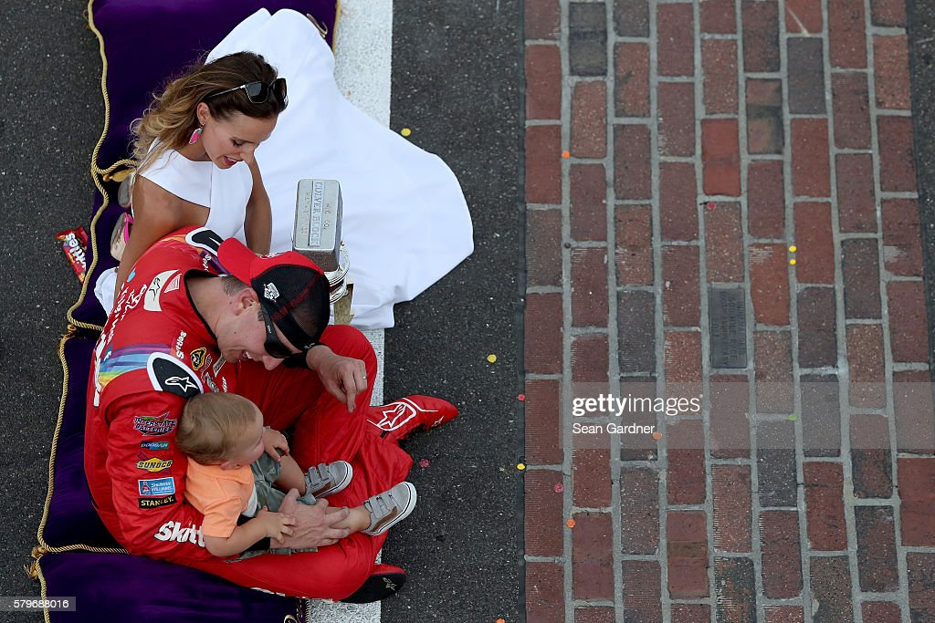 Kyle Busch, driver of the #18 Skittles Toyota, celebrates with his wife, Samantha, and son, Brexton, after winning the NASCAR Sprint Cup Series Crown Royal Presents the Combat Wounded Coalition 400 at Indianapolis Motor Speedway on July 24, 2016 in Indianapolis, Indiana.