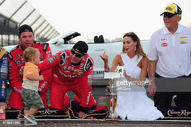 Kyle Busch driver of the Skittles Toyota celebrates with his wife Samantha son Brexton and team owner Joe Gibbs after winning the NASCAR Sprint Cup...