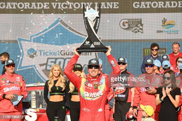 Kyle Busch, driver of the Skittles Toyota, celebrates with the trophy after winning the Monster Energy NASCAR Cup Series TicketGuardian 500 at ISM...