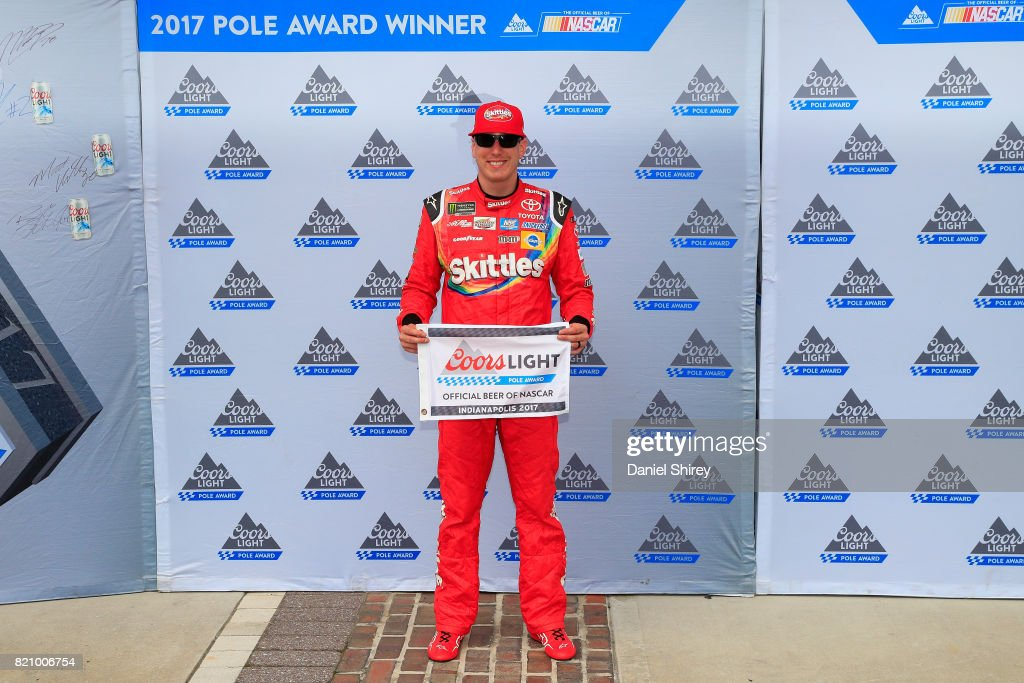 Kyle Busch, driver of the #18 Skittles Toyota, poses with the Coors Light Pole Award after qualifying for pole position for the Monster Energy NASCAR Cup Series Brickyard 400 at Indianapolis Motorspeedway on July 22, 2017 in Indianapolis, Indiana.