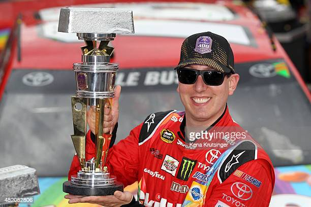 Kyle Busch driver of the Skittles Toyota poses with the trophy in Victory Lane after winning the NASCAR Sprint Cup Series Crown Royal Presents the...