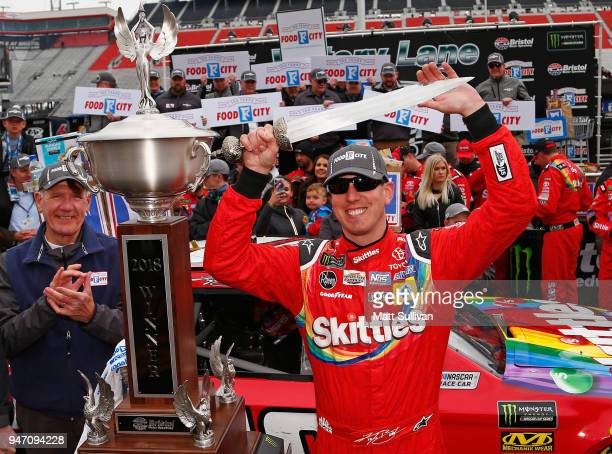 Kyle Busch driver of the Skittles Toyota poses with the trophy in victory lane after winning the rain delayed Monster Energy NASCAR Cup Series Food...