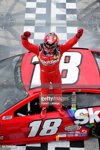 Kyle Busch driver of the Skittles Toyota stands on his car in celebration after winning the rain delayed Monster Energy NASCAR Cup Series Food City...