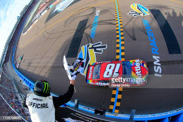 Kyle Busch driver of the Skittles Toyota takes the checkered flag to win the Monster Energy NASCAR Cup Series TicketGuardian 500 at ISM Raceway on...