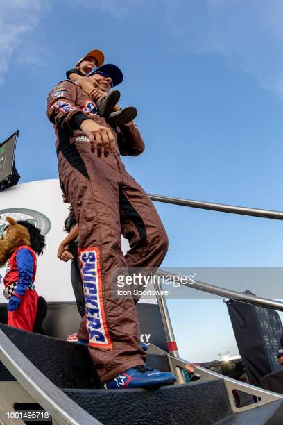 Kyle Busch driver of the Snickers Intense Toyota walks with his son on his shoulders during driver introductions before the Monster Energy NASCAR Cup...