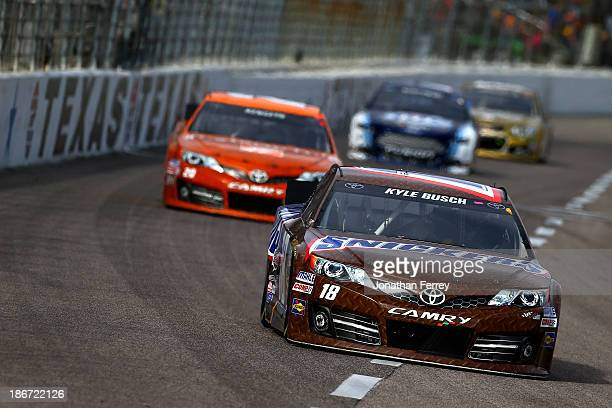 """Kyle Busch, driver of the Snickers Toyota, leads Matt Kenseth, driver of the Home Depot """"Let's Do This"""" Toyota, and Brad Keselowski, driver of the..."""