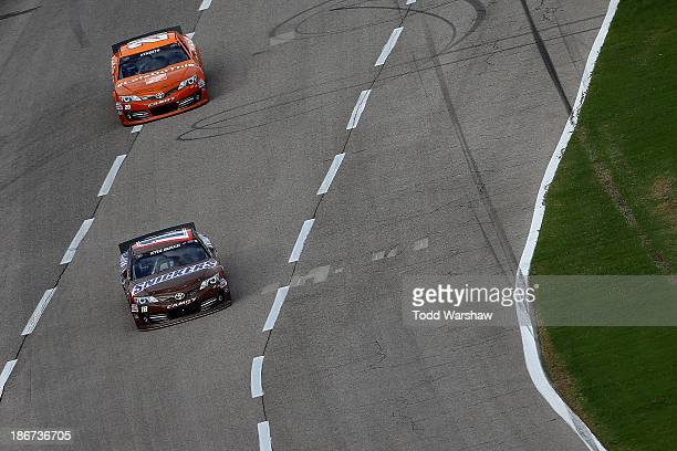 """Kyle Busch, driver of the Snickers Toyota, leads Matt Kenseth, driver of the Home Depot """"Let's Do This"""" Toyota, during the NASCAR Sprint Cup Series..."""