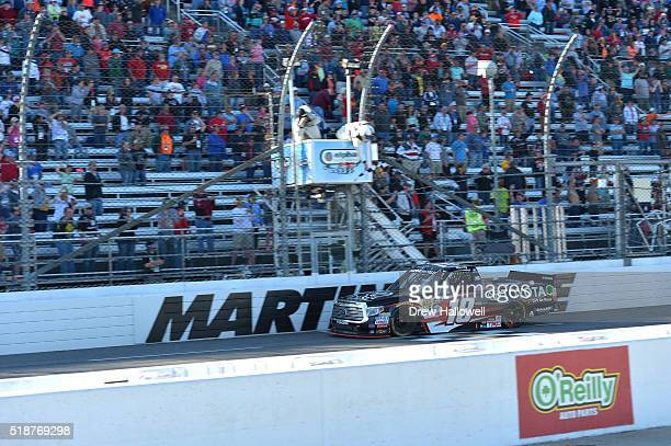 Kyle Busch driver of the Toyota Toyota takes the checkered flag to win the NASCAR Camping World Truck Series Alpha Energy Solutions 250 at...