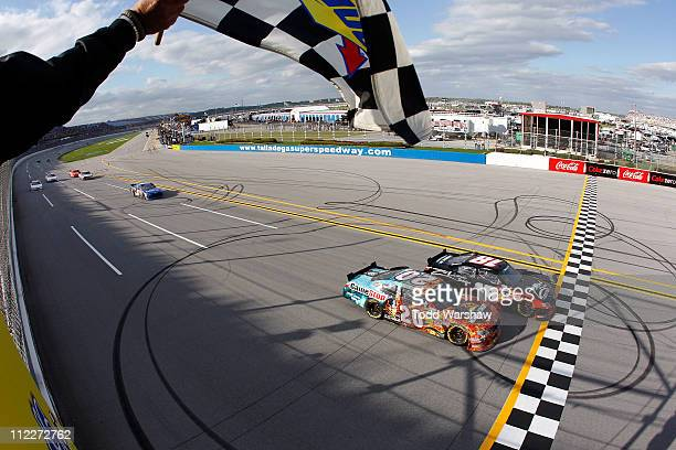 Kyle Busch driver of the ZLine Designs Toyota crosses the finish line ahead of Joey Logano driver of the GameStop Toyota to win the NASCAR Nationwide...