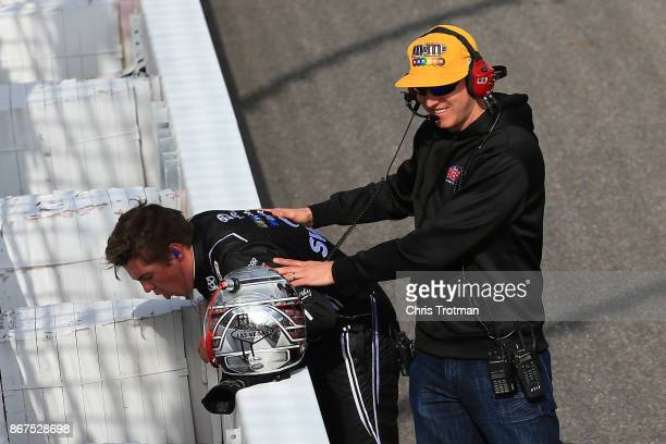 Kyle Busch team owner and driver of the MM's Halloween Toyota checks on Noah Gragson driver of the Switch Toyota after winning the NASCAR Camping...