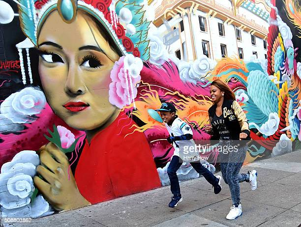 Kyle Bynes Jr and Tiye Young run along the sidewalk in Chinatown on February 6 2016 in San Francisco United States