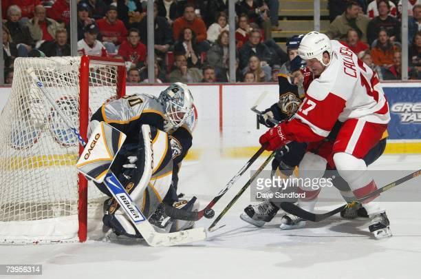 Kyle Calder of the Detroit Red Wings skates to the net for a shot on goal against goaltender Chris Mason of the Nashville Predators during their NHL...