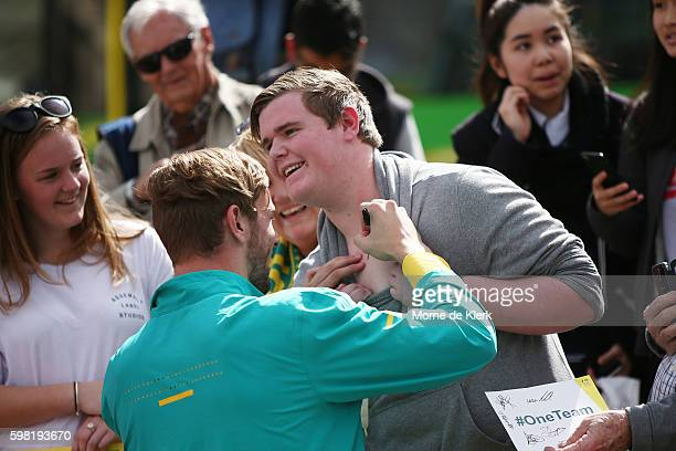 Kyle Chalmers sighs the chest of a spectator during Welcome Home celebrations for the Australian Olympic Games Team at Victoria Square on September 1...