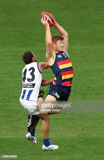 Kyle Cheney of the Crows marks the ball against Sam Gibson of the Kangaroos during the round one AFL match between the Adelaide Crows and the North...