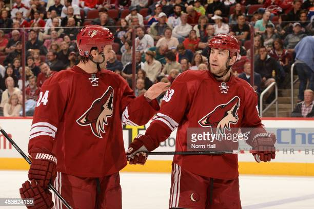 Kyle Chipchura and teammate Derek Morris of the Phoenix Coyotes talk during a stop in play against the Edmonton Oilers at Jobing.com Arena on April...