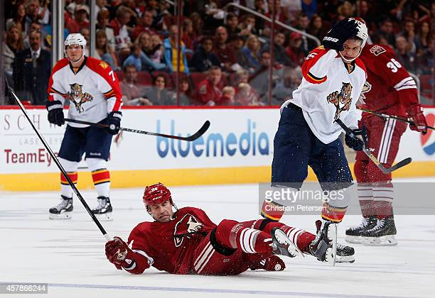 Kyle Chipchura of the Arizona Coyotes falls to the ice after being chekced by Aleksander Barkov of the Florida Panthers during the first period of...