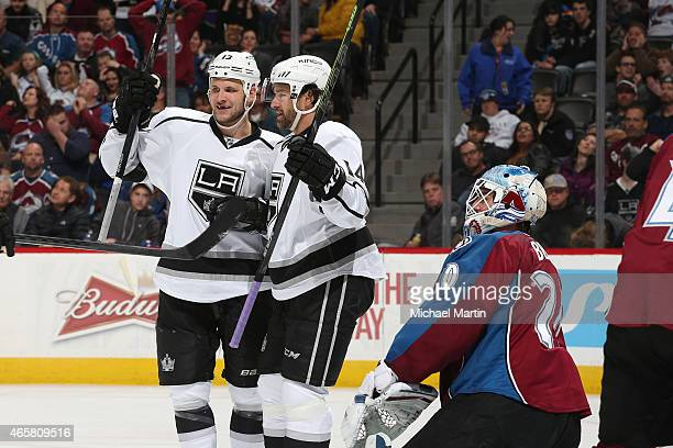 Kyle Clifford and Justin Williams of the Los Angeles Kings celebrate after scoring as goaltender Reto Berra of the Colorado Avalanche reacts at the...