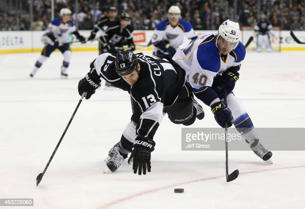 Kyle Clifford of the Los Angeles Kings and Maxim Lapierre of the St Louis Blues fight for the puck in the second period at Staples Center on December...