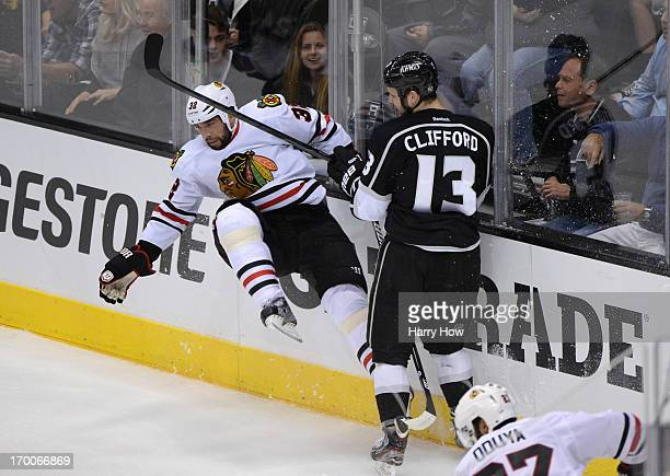 Kyle Clifford of the Los Angeles Kings checks Michal Rozsival of the Chicago Blackhawks at the end boards in the second period of Game Four of the...
