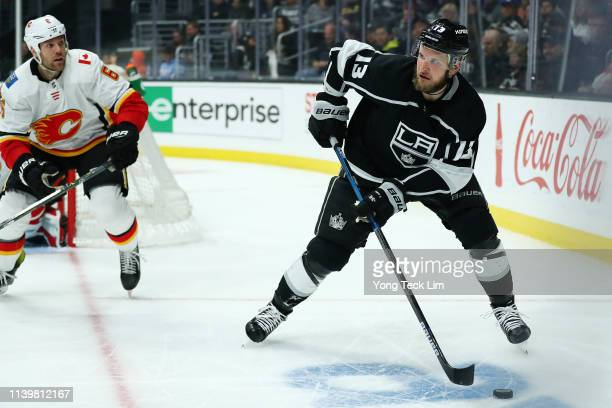 Kyle Clifford of the Los Angeles Kings controls the puck against Dalton Prout of the Calgary Flames during the second period at Staples Center on...