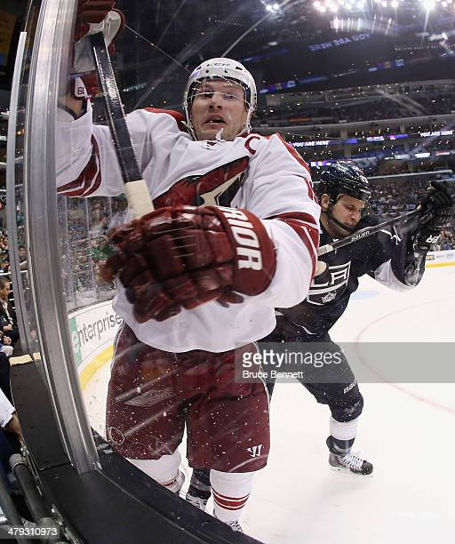 Kyle Clifford of the Los Angeles Kings hits Shane Doan of the Phoenix Coyotes into the boards during the second period at the Staples Center on March...