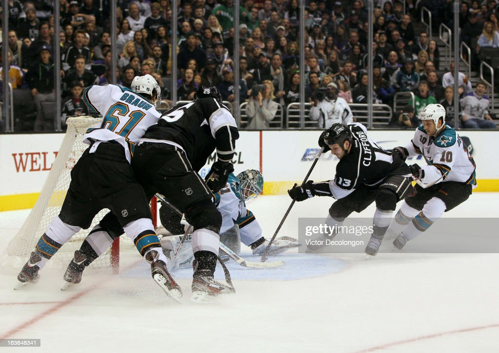 Kyle Clifford #13 of the Los Angeles Kings jams the puck past goaltender Antti Niemi #31 of the San Jose Sharks for a goal in the second period during the NHL game at Staples Center on March 16, 2013 in Los Angeles, California.