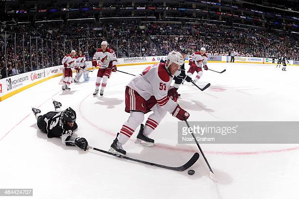 Kyle Clifford of the Los Angeles Kings reaches for the puck against Derek Morris of the Phoenix Coyotes at Staples Center on April 2, 2014 in Los...