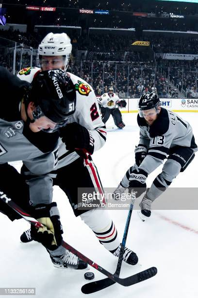 Kyle Clifford of the Los Angeles Kings reaches for the puck as Duncan Keith of the Chicago Blackhawks and Austin Wagner of the Los Angeles Kings...
