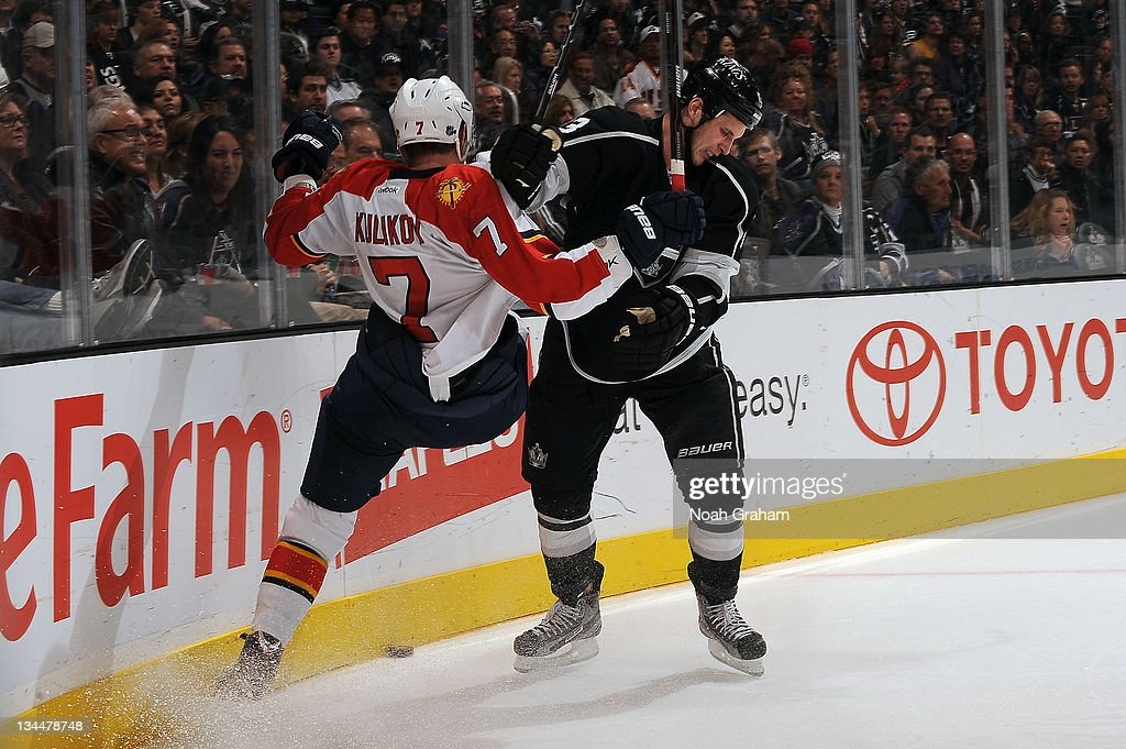 Kyle Clifford #13 of the Los Angeles Kings throws the check against Dmitry Kulikov #7 of the Florida Panthers at Staples Center on December 1, 2011 in Los Angeles, California.