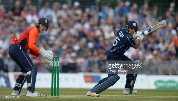 Kyle Coetzer of Scotland hits out watched by Sam Billings of England during the OneDay International match between Scotland and England at Grange...