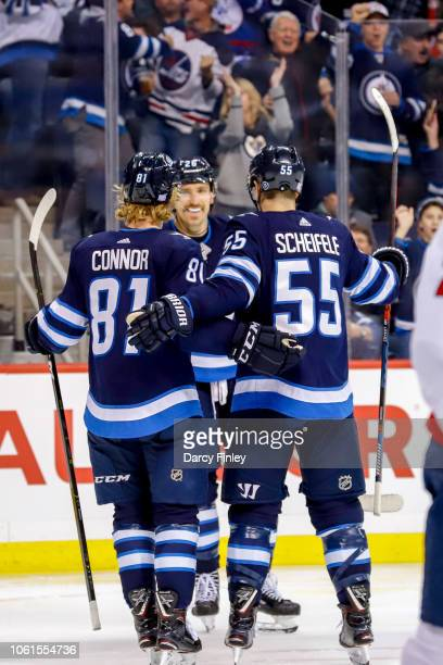 Kyle Connor Blake Wheeler and Mark Scheifele of the Winnipeg Jets celebrate a second period goal against the Washington Capitals at the Bell MTS...