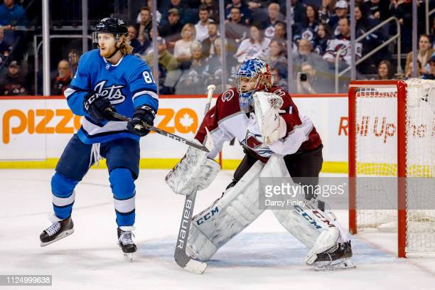 Kyle Connor of the Winnipeg Jets and goaltender Semyon Varlamov of the Colorado Avalanche keep an eye on the play during third period action at the...