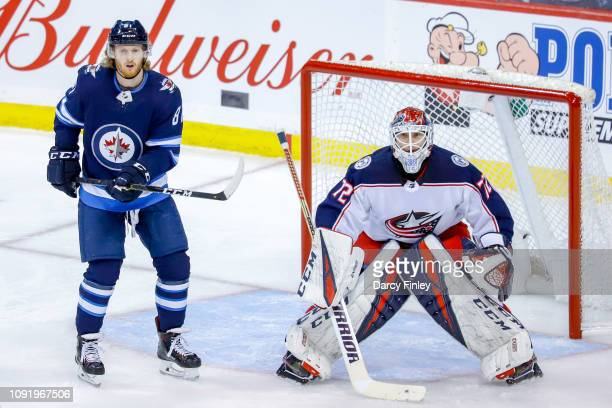 Kyle Connor of the Winnipeg Jets and goaltender Sergei Bobrovsky of the Columbus Blue Jackets keep an eye on the play during second period action at...