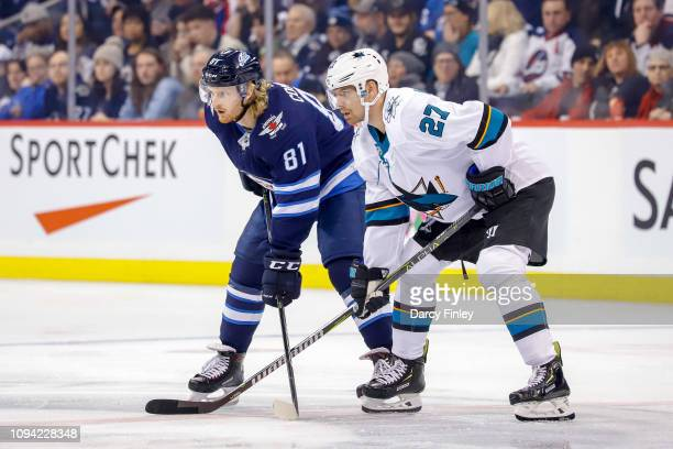 Kyle Connor of the Winnipeg Jets and Joonas Donskoi of the San Jose Sharks get set during a first period faceoff at the Bell MTS Place on February 5...