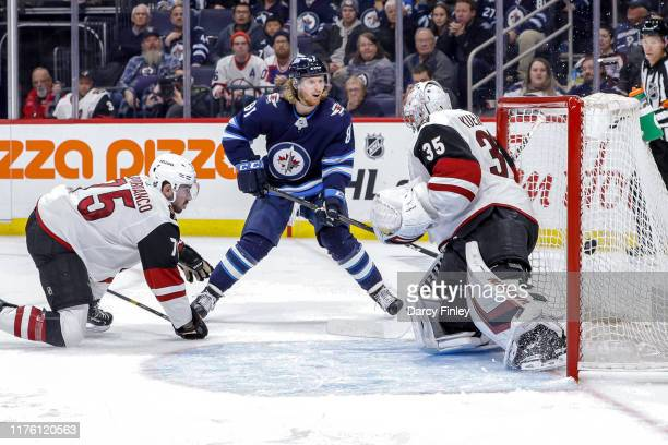 Kyle Connor of the Winnipeg Jets and Kyle Capobianco of the Arizona Coyotes watch as the puck gets behind goaltender Darcy Kuemper for a third period...
