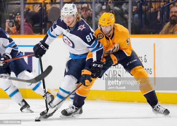 Kyle Connor of the Winnipeg Jets battles for the puck against Austin Watson of the Nashville Predators at Bridgestone Arena on January 17 2019 in...