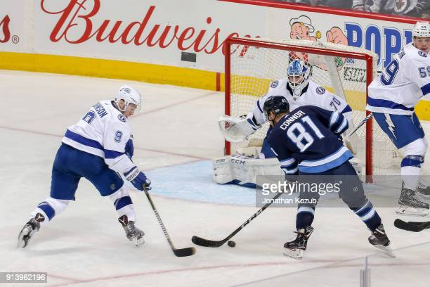 Kyle Connor of the Winnipeg Jets battles Tyler Johnson of the Tampa Bay Lightning as he tries to get a shot on goaltender Louis Domingue during...