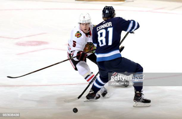 Kyle Connor of the Winnipeg Jets blocks Connor Murphy of the Chicago Blackhawks during third period action at the Bell MTS Place on March 15 2018 in...