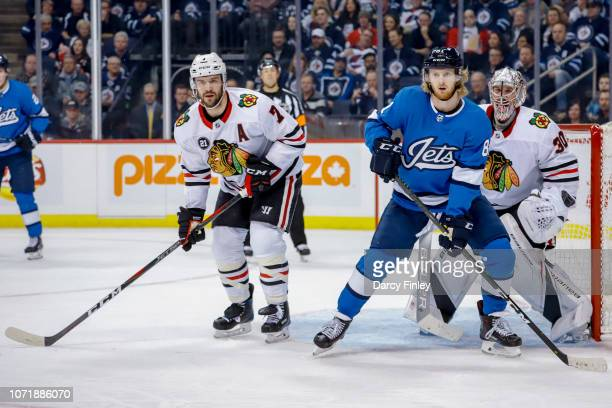 Kyle Connor of the Winnipeg Jets Brent Seabrook and goaltender Cam Ward of the Chicago Blackhawks keep an eye on the play during first period action...