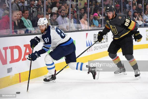 Kyle Connor of the Winnipeg Jets carries the puck against Nate Schmidt of the Vegas Golden Knights during the first period in Game Four of the...
