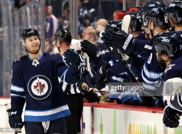 Kyle Connor of the Winnipeg Jets celebrates his first period goal against the Chicago Blackhawks with teammates at the bench at the Bell MTS Place on...