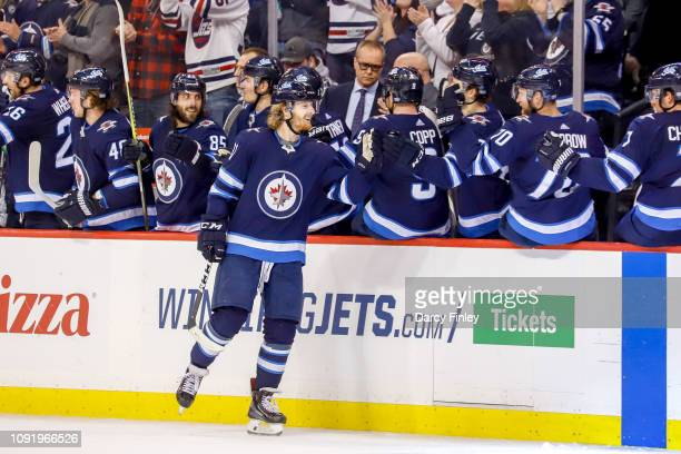 Kyle Connor of the Winnipeg Jets celebrates his third period goal against the Columbus Blue Jackets with teammates at the bench at the Bell MTS Place...