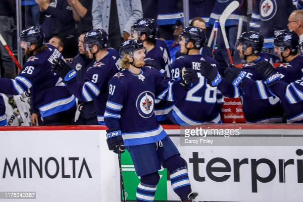 Kyle Connor of the Winnipeg Jets celebrates his third period goal against the Minnesota Wild with teammates at the bench at the Bell MTS Place on...