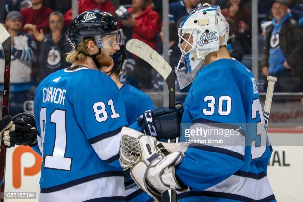 Kyle Connor of the Winnipeg Jets congratulates teammate Laurent Brossoit following a 31 victory over the Carolina Hurricanes at the Bell MTS Place on...