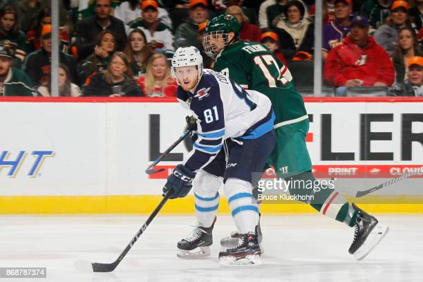 Kyle Connor of the Winnipeg Jets looks for a pass with Marcus Foligno of the Minnesota Wild defending during the game at the Xcel Energy Center on...