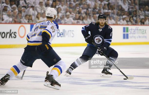 Kyle Connor of the Winnipeg Jets looks to pass in front of Alex Pietrangelo of the St Louis Blues in Game Five of the Western Conference First Round...