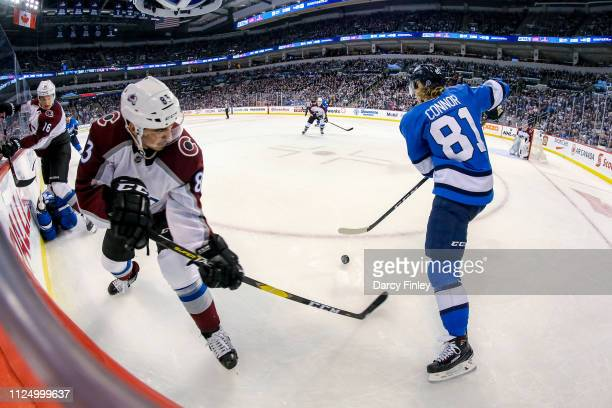 Kyle Connor of the Winnipeg Jets play the puck away from Matt Nieto of the Colorado Avalanche during third period action at the Bell MTS Place on...