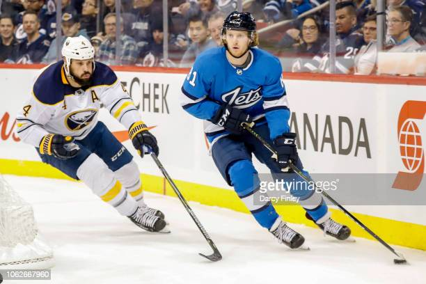 Kyle Connor of the Winnipeg Jets plays the puck along the boards as Zach Bogosian of the Buffalo Sabres gives chase during first period action at the...